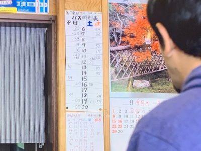 店内の手書きのバスの時刻表を見る民生